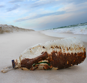 oil covered plastic bottle on beach