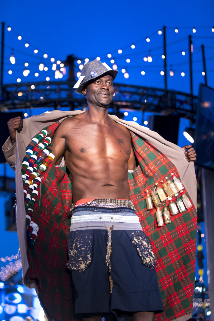 "This guest model is wearing ""Washed Up Saleman."" Men's briefs, board shorts, hats and clothing tags are a frequent find on any beach. Not to mention the single-use plastic bottles on the inside of the jacket. (Photo by David Young-Wolff)"