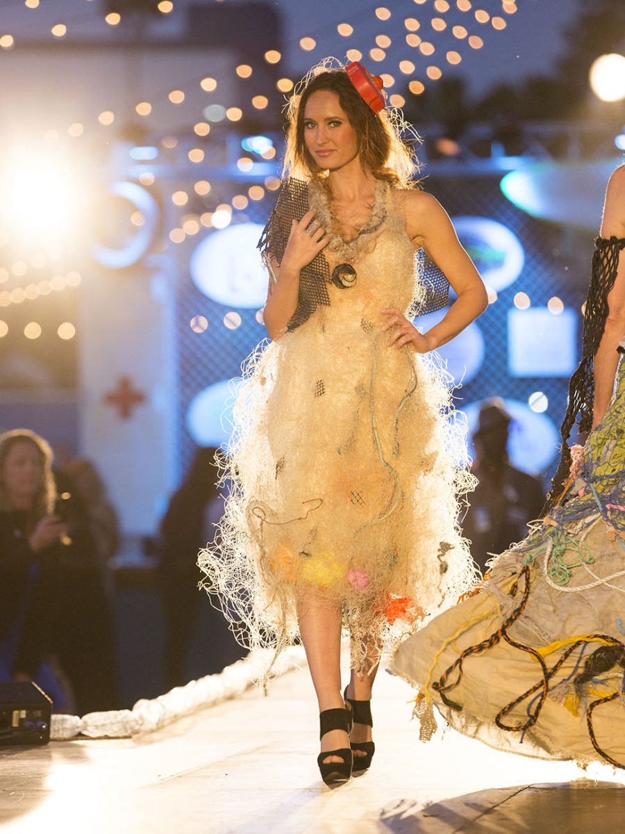 "This guest model is wearing ""A Captive Audience,"" a dress made from netting found floating in the Pacific Garbage Patch by Captain Charles Moore. Beach toys are held captive and have nowhere to go. (Photo by Nicola Buck)"
