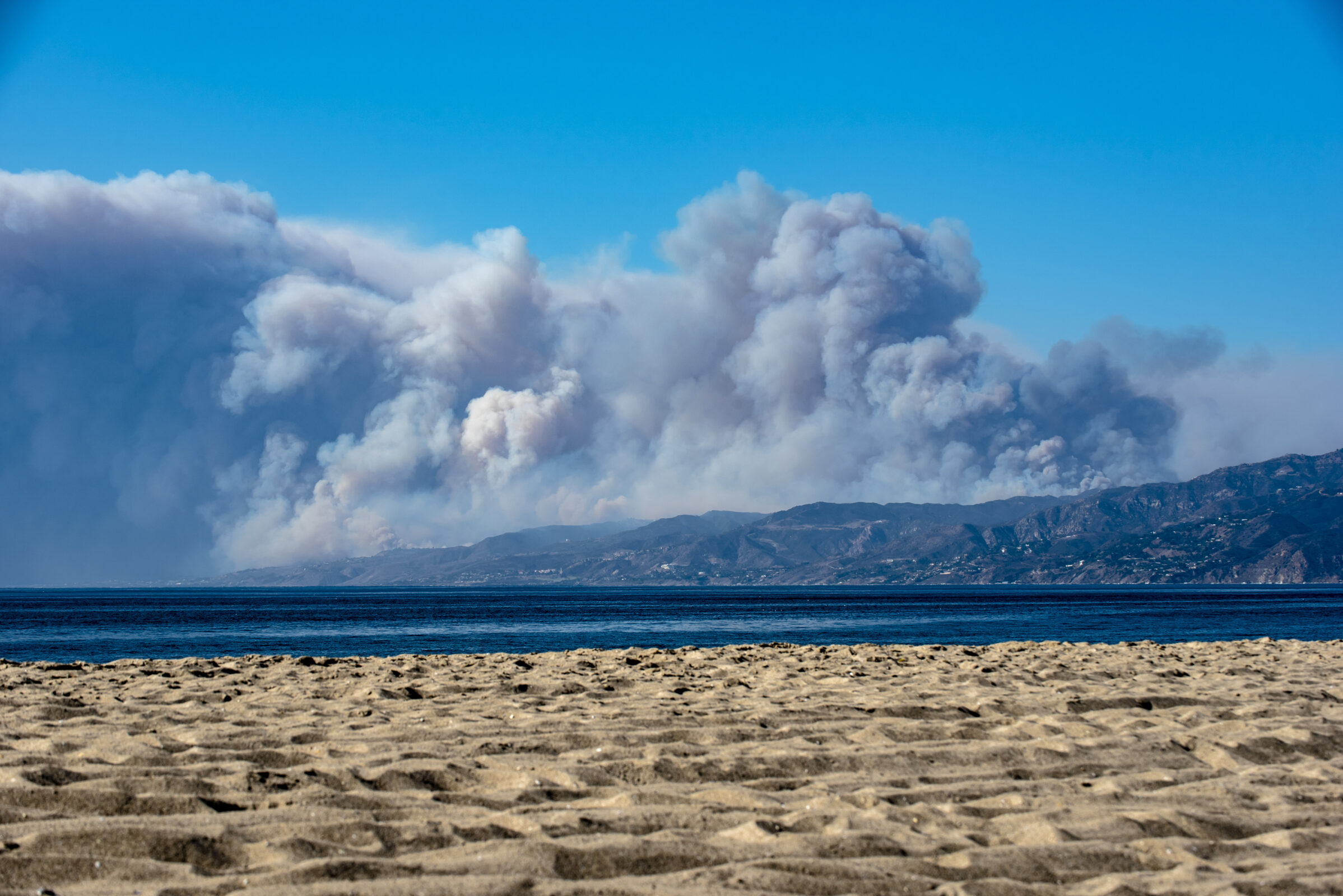 Large plumes of smoke rise from the Woolsey Fire burning in Malibu, California. Camera angle is looking across Santa Monica Bay towards Malibu and Santa Monica Mountains.